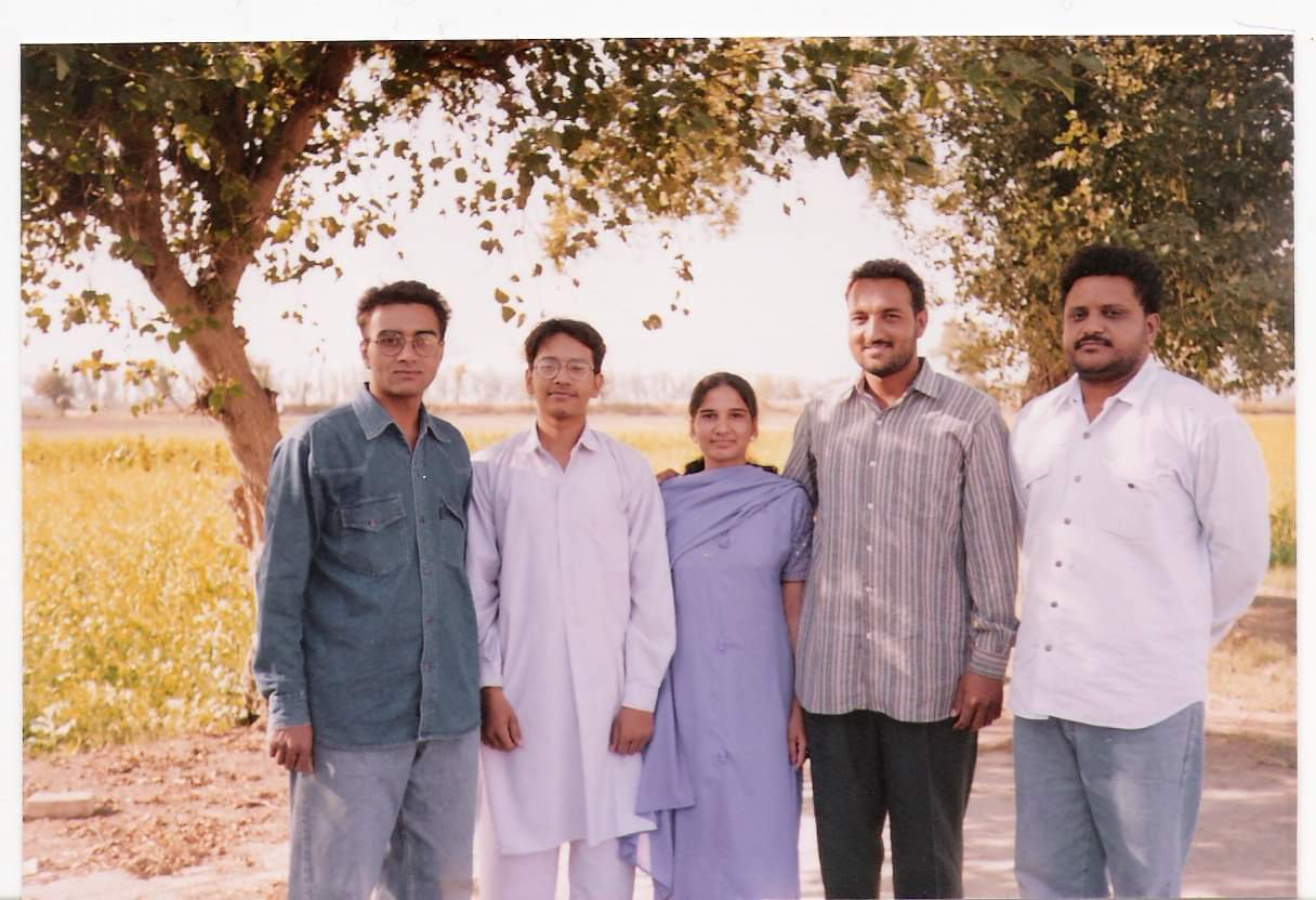 5 people pose under trees and in front of a farm
