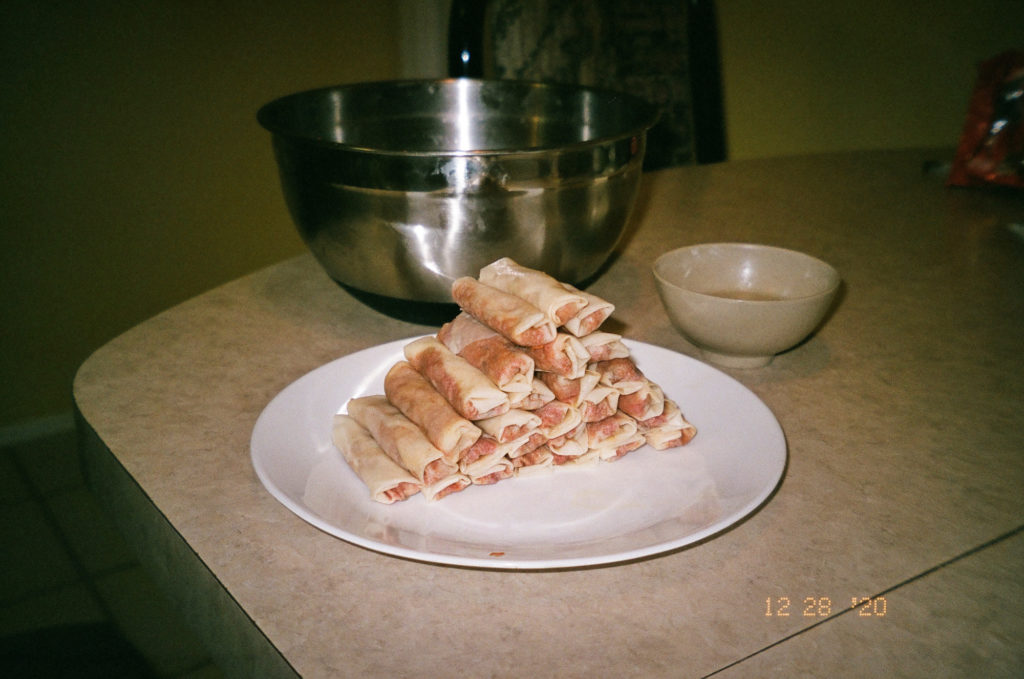 A white plate stacked high with lumpia.