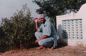 A man wearing a turban is squatting on the ground next to a tree.
