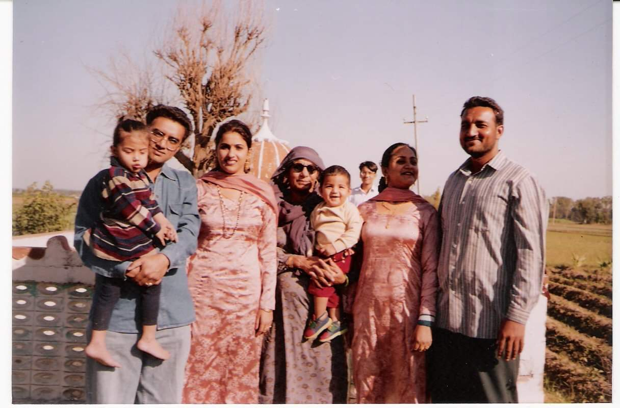 5 adults and 2 children stand in front of a farm.
