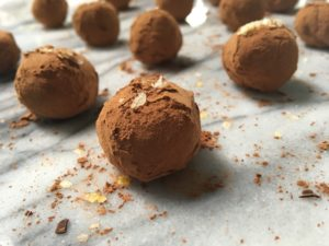 an array of chocolate truffles rolled in cocoa and sprinkled with lemon salt are arrayed on a marble slab.