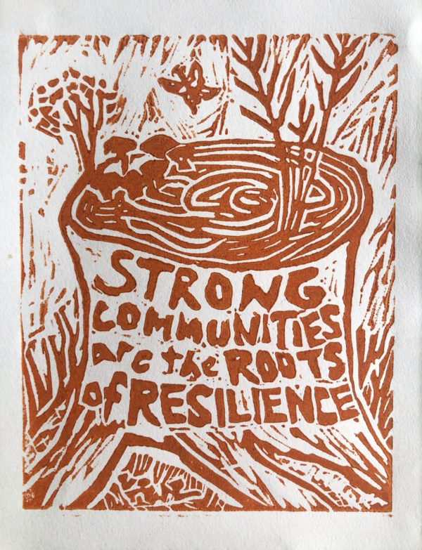 A tree stump with mushrooms, flowers and grasses growing out of the top, and 'strong communities are the roots of resilience' written across the front. A butterfly hovers above, and there are markings behind and around the stump. The print is carved and has rugged lines with burnt orange ink.